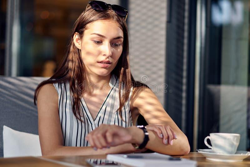 De bedrijfsvrouw is laat op tijd, in zeven haasten controleert zij de uiterste termijn op haar klassiek polshorloge in bureau royalty-vrije stock afbeelding