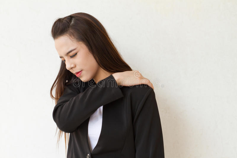 De bedrijfsvrouw lijdt aan schouderpijn of stijfheid royalty-vrije stock afbeelding