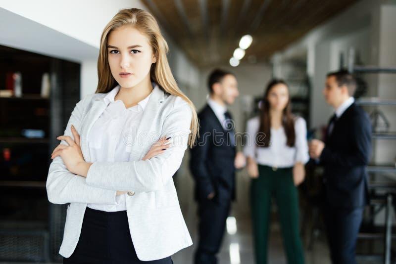 De bedrijfsvrouw met haar personeel, mensen groepeert zich op achtergrond op modern helder kantoor stock afbeelding