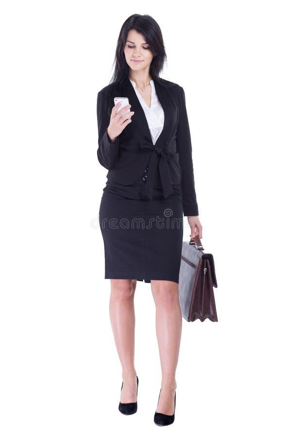 De bedrijfsvrouw met leeraktentas leest SMS op haar smartphone royalty-vrije stock afbeeldingen