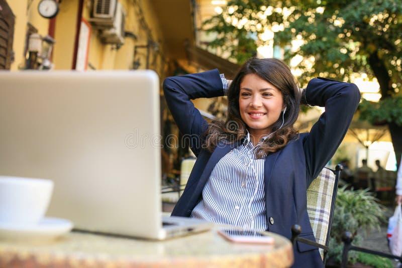 De bedrijfsvrouw neemt een onderbreking van het werken, gebruikend tijd aan listenin stock foto