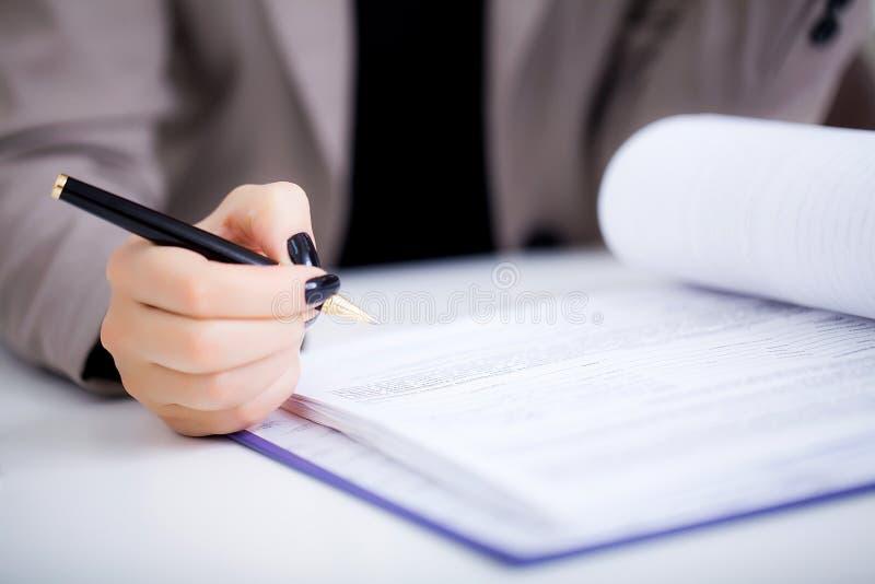 De bedrijfsvrouw ondertekent een contract, bedrijfscontractdetails stock foto's