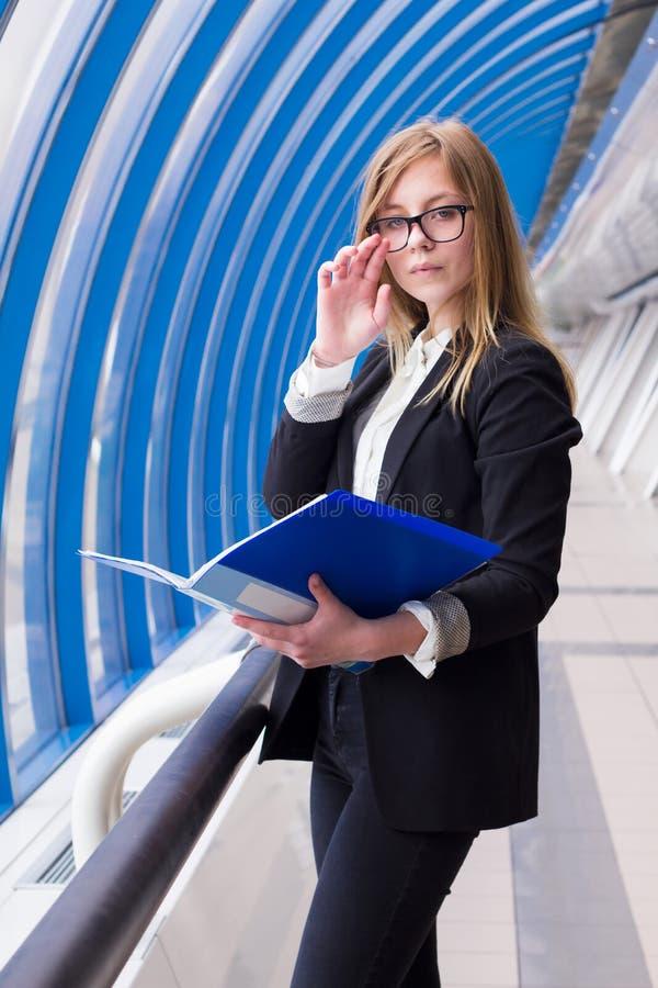 De bedrijfsvrouw past glazen en holding aan een omslag met in hand documenten stock afbeelding