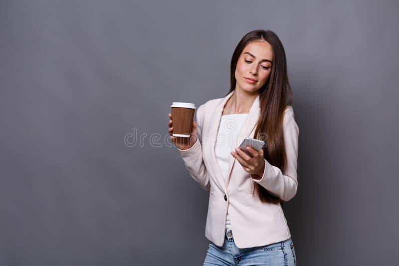 De bedrijfsvrouw roept mobiele telefoon en drinkt koffie op het werk stock foto's