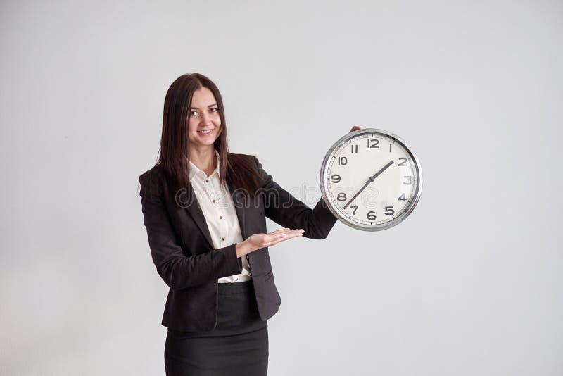 De bedrijfsvrouw toont op de grote ronde klok, op een grijze muurachtergrond in het bureau royalty-vrije stock fotografie