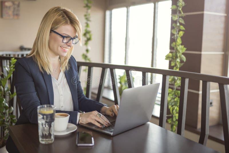 De bedrijfsvrouw werkt aan computer en het drinken kop van koffie en glas water in een koffiewinkel, restaurant royalty-vrije stock afbeelding