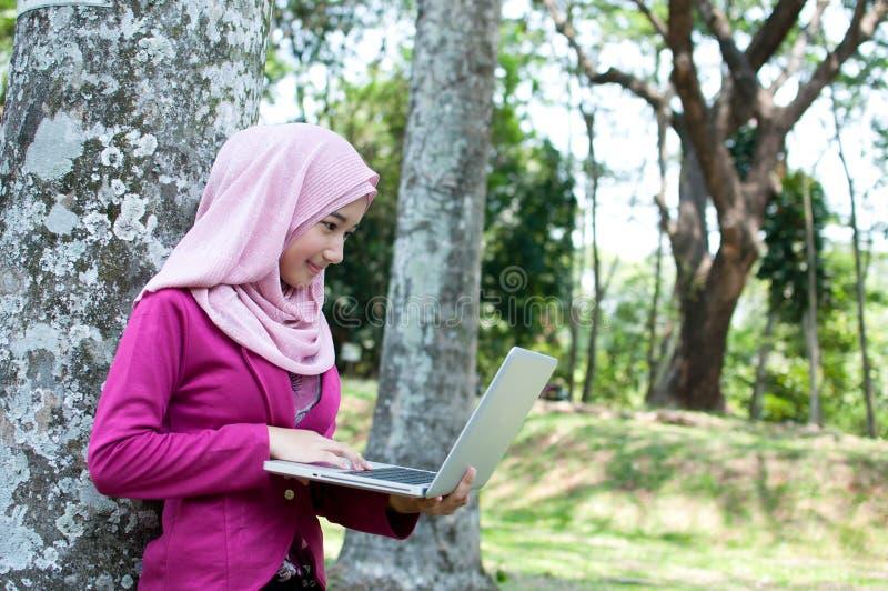 De bedrijfsvrouw werkt met llaptop bij tuin stock foto