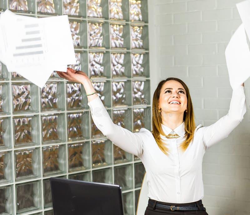 De bedrijfsvrouw werpt op haar documenten damemanager die met geluk glimlachen royalty-vrije stock foto's