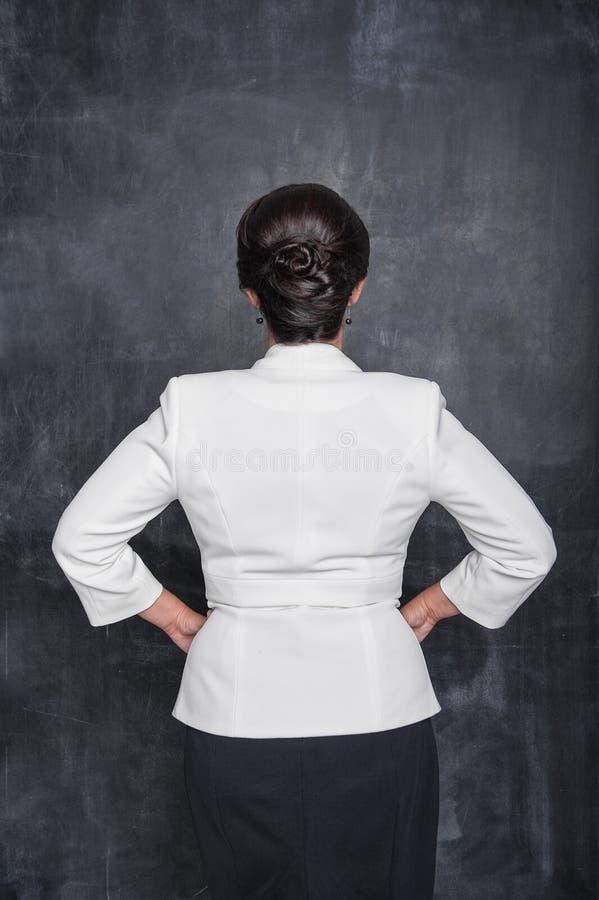 De bedrijfsvrouw in witte blazer die stelt op bordachtergrond achteruitgaan royalty-vrije stock afbeelding