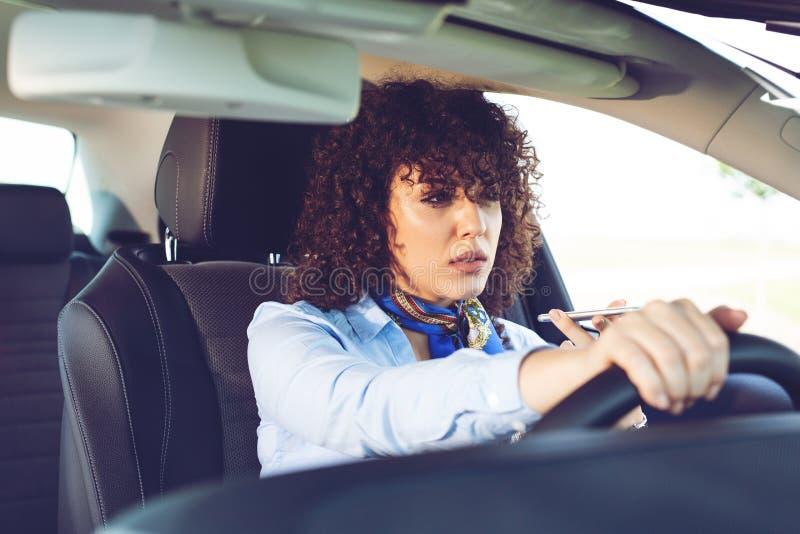 De bedrijfsvrouw zit in de auto en spreekt telefonisch royalty-vrije stock foto