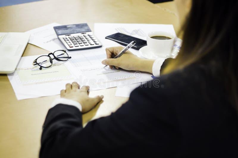 De bedrijfsvrouwen analyseren de vergadering van de aandeelhouders van de documentenpresentatie, met grafieken en marketing plang stock afbeelding