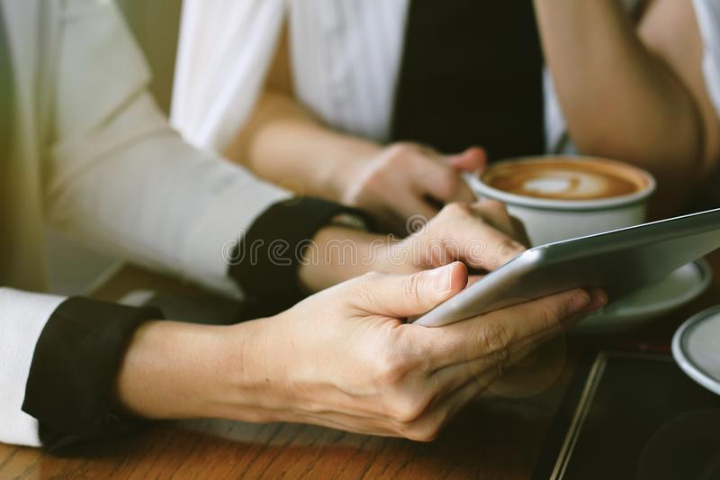 De bedrijfsvrouwen die tabletpc in koffiekoffie met behulp van voor bespreken project royalty-vrije stock fotografie