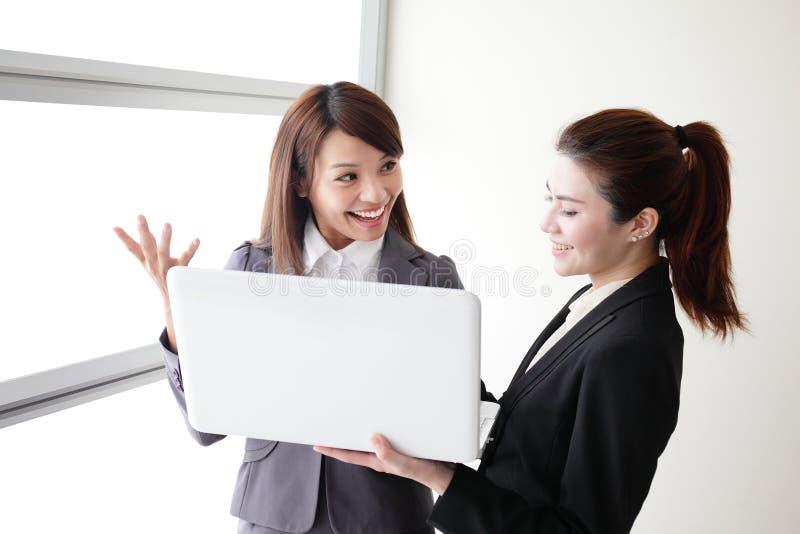 De bedrijfsvrouwen kijken en glimlachen gesprek stock afbeelding