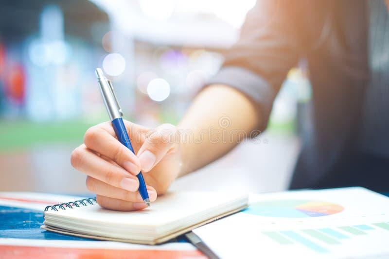 De bedrijfsvrouwen nemen nota's over bedrijfsstatistieken en grafieken stock afbeelding