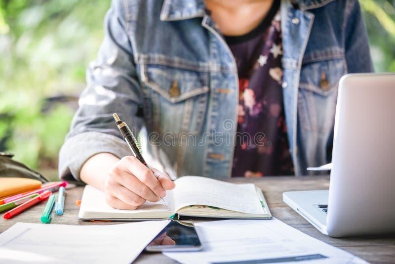 De bedrijfsvrouwen werkt aan bureaubureau met haar computer laptop en het schrijven rekeningen voor investering het binnenlandse  stock fotografie