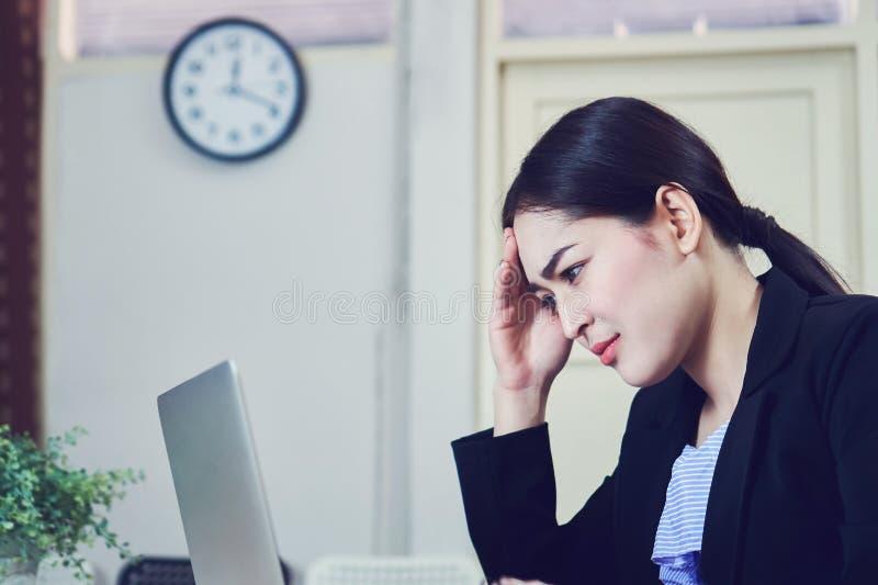 De bedrijfsvrouwen zitten lange tijd en spannen het computerscherm Omdat het werk is overbelast stock foto
