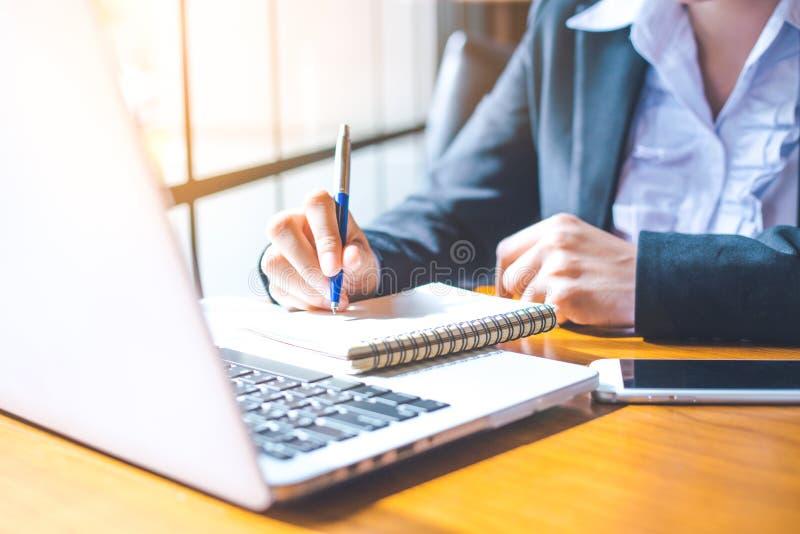 De bedrijfsvrouwenhand die in een laptop computer werken schrijft op n stock foto