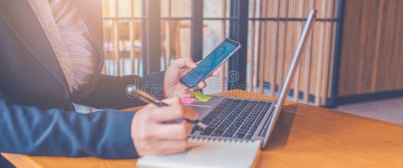 De bedrijfsvrouwenhand gebruikt mobiele telefoons, de grafieken van de het werkanalyse van het schermvertoningen, en zij neemt no stock foto
