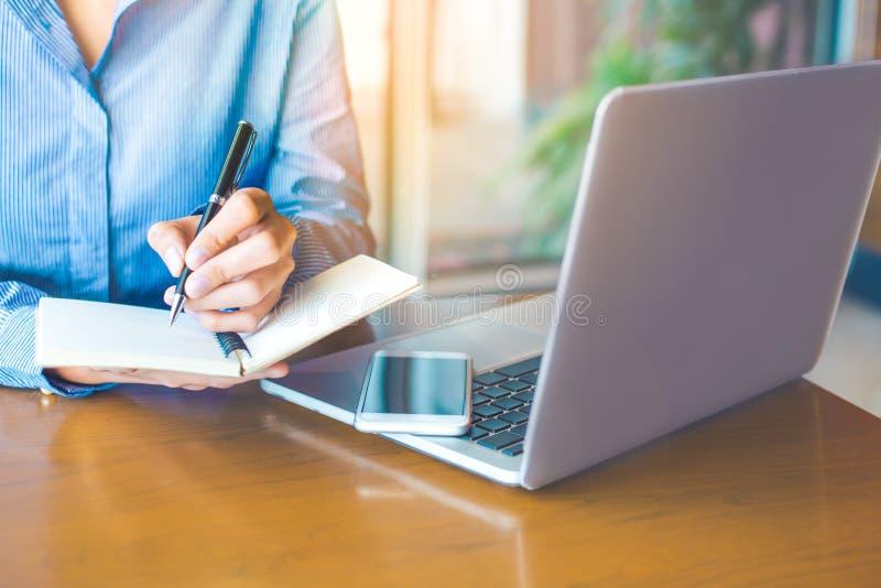 De bedrijfsvrouwenhand schrijft op blocnote met pen in bureau Op de houten lijst zijn er celtelefoons en laptops stock foto's