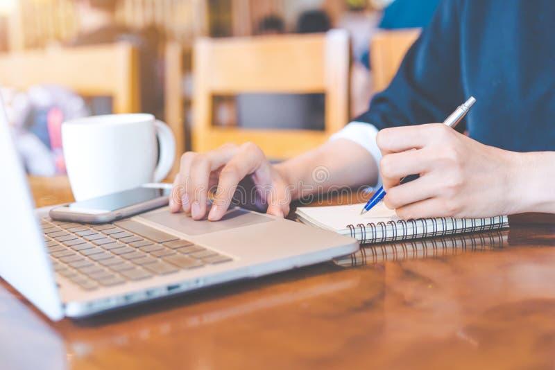 De bedrijfsvrouwenhand werkt aan een een notitieboekjecomputer en writin stock foto's