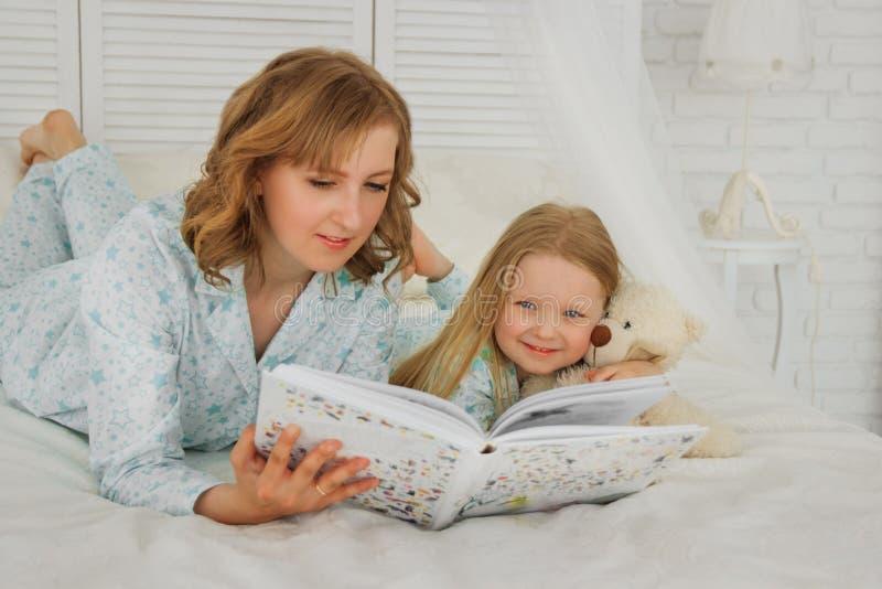 De bedtijd van de familielezing Vrij jonge moeder die een boek lezen aan haar dochter De moeder leest een sprookje aan haar docht stock afbeeldingen