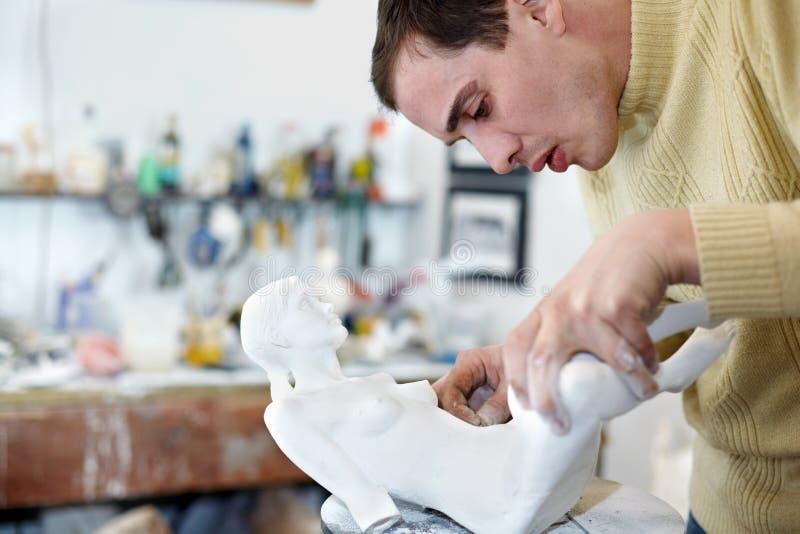 De beeldhouwer maakt zorgvuldig benen aan beeldje vast stock foto's
