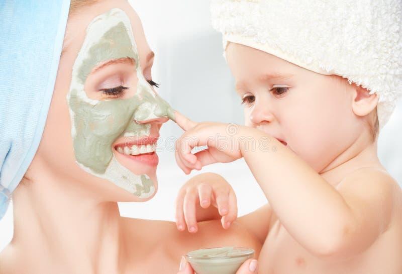 De behandeling van de familieschoonheid in de badkamers moeder en dochter het babymeisje maakt een masker voor gezichtshuid royalty-vrije stock afbeeldingen