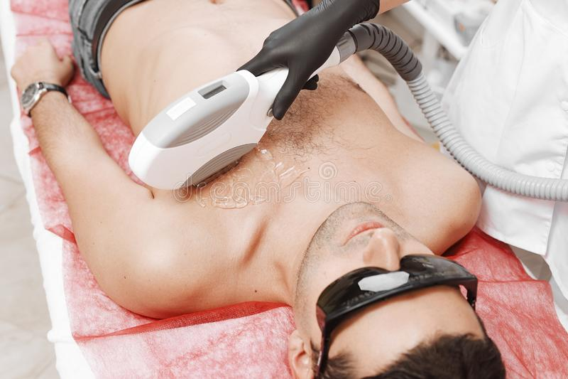 De Behandeling van therapeutgiving laser epilation aan de Jonge Mens in Kuuroord stock afbeelding