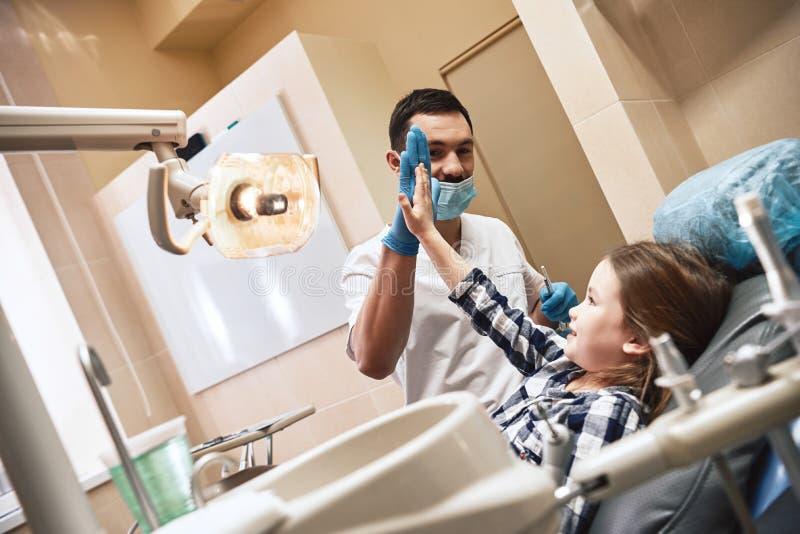 De behandeling voor tandbezorgdheid Jong geitje op het tandkantoor Een kind is gelukkig na tandbehandeling en het geven van hoog- royalty-vrije stock foto