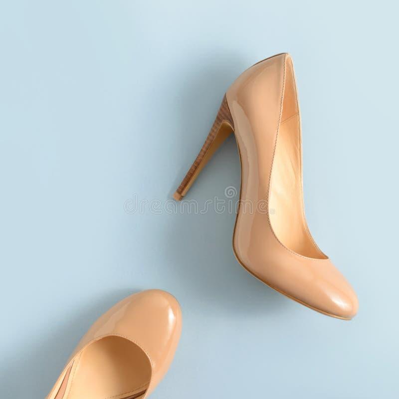 De beige hoge vrouwen hielen schoenen op roze achtergrond De manierblog ziet eruit stock foto