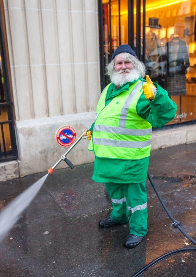 De bejaarde arbeider wast straat stock foto
