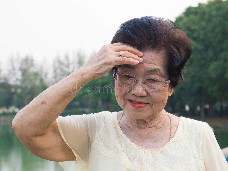 De bejaarde Aziatische vrouw droeg glazen zij was niet comfortabel met hoofdpijnen Wanneer hogere vrouw die in het park lopen stock afbeelding