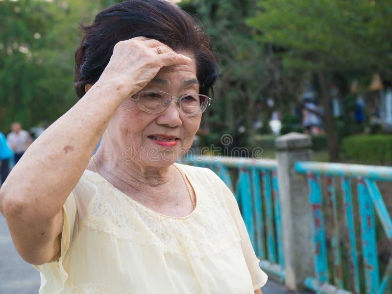 De bejaarde Aziatische vrouw droeg glazen zij was niet comfortabel met hoofdpijnen Wanneer hogere vrouw die in het park lopen royalty-vrije stock foto's