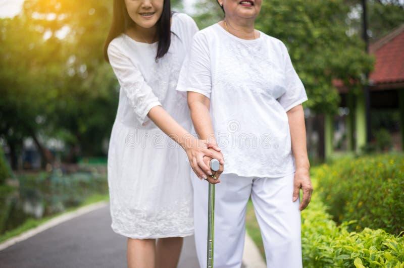 De bejaarde Aziatische vrouwen die fysiek met stok lopen te doen openlucht, Dochter nemen zorg en de steun, sluit omhoog stock foto's