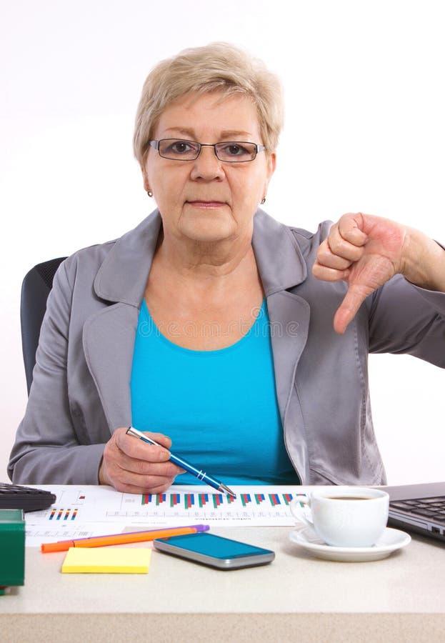 De bejaarde bedrijfsvrouw die duimen tonen verslaat en bij haar bureau in bureau, bedrijfsconcept werken stock afbeeldingen