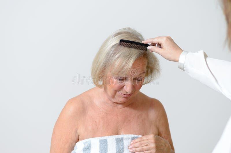 De bejaarde dame krijgt haar haar gekamd royalty-vrije stock fotografie