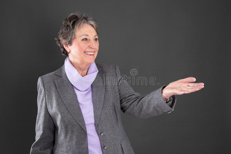 De bejaarde dame stelt iets voor - oudere die vrouw op zwarte wordt geïsoleerd royalty-vrije stock foto