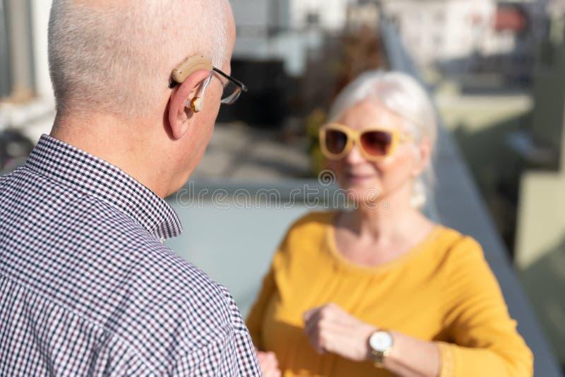 De bejaarde, dove mens gebruikt een gehoorapparaat stock afbeelding
