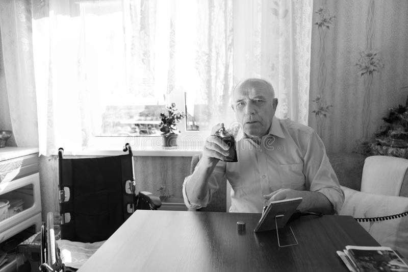 De bejaarde Fles van Holdingsaftershave in Zwart-wit stock fotografie