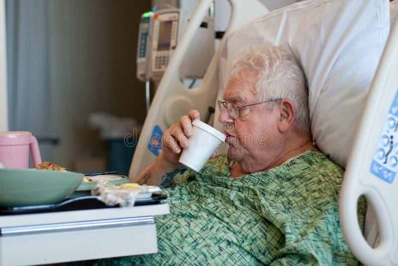 De bejaarde mannelijke het ziekenhuispatiënt drinkt water royalty-vrije stock fotografie