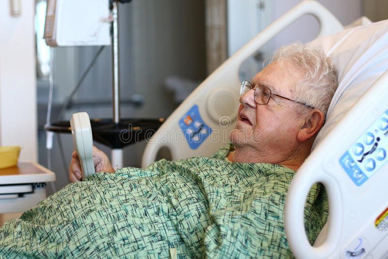 De bejaarde mannelijke het ziekenhuispatiënt houdt TV ver stock foto's
