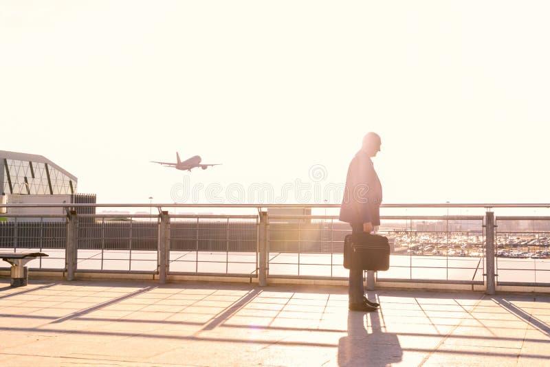 De bejaarde mannelijke zakenman was laat voor de vlucht, vloog het vliegtuig weg, het concept laat het onderbreken van de overeen stock foto