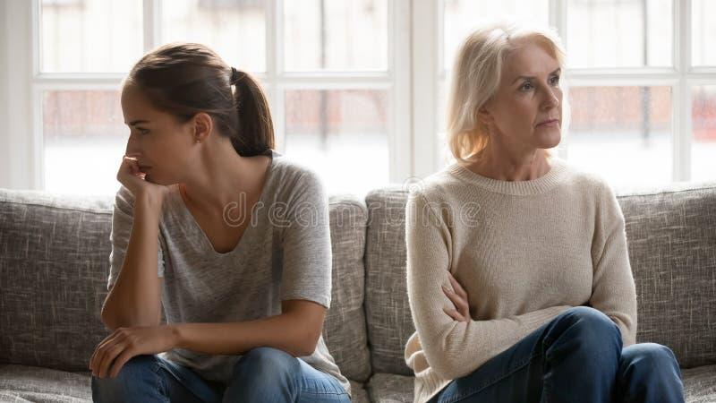 De bejaarde moeder en de gegroeide dochter zitten afzonderlijk op laag royalty-vrije stock afbeeldingen