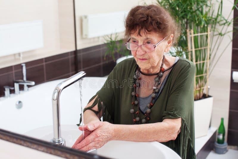 De bejaarde oude vrouw wast haar handen stock fotografie
