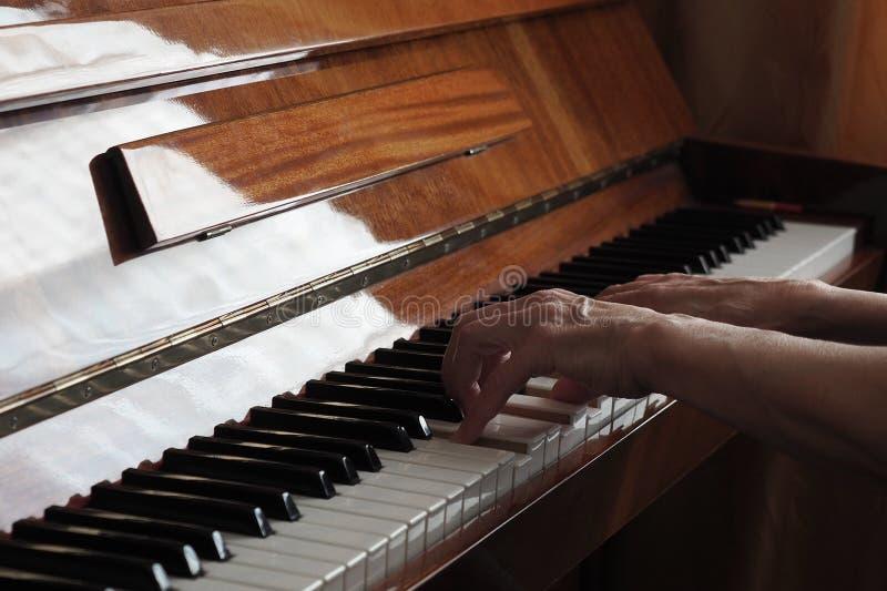 De bejaarde persoonshanden die de piano spelen, sluiten omhoog royalty-vrije stock fotografie