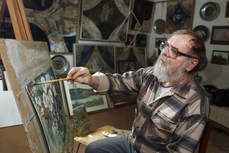 De bejaarde schilder met baard en glazen trekt een bloemenbeeld door olieverf in kunstworkshop royalty-vrije stock fotografie