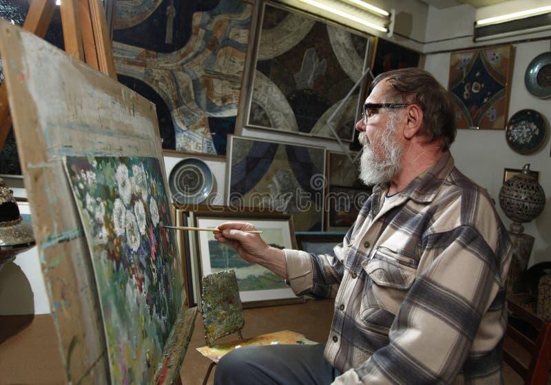 De bejaarde schilder met baard en glazen trekt een bloemenbeeld door olieverf in kunstworkshop stock afbeeldingen