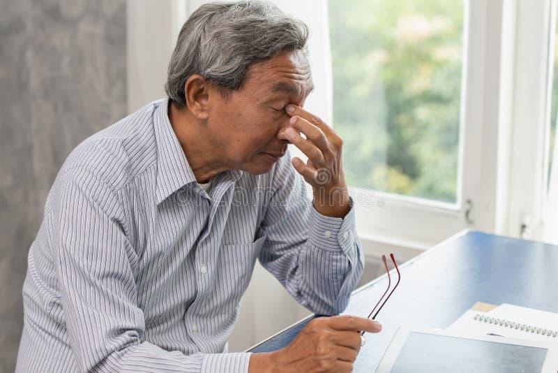 De bejaarden beklemtonen vermoeid en holding zijn neus aan de moeheid van de sinuspijn lijdt royalty-vrije stock foto