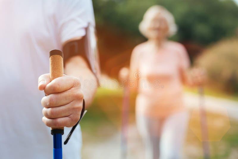 De bejaarden bemannen hand houdend een het lopen pool stock afbeelding