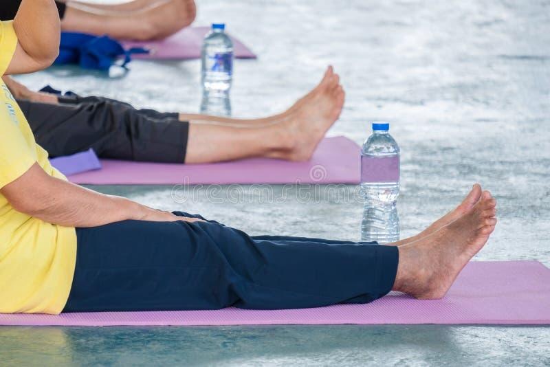 De bejaarden in een yoga oefenen houding uit stock foto's